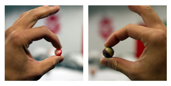 Holding .50 caliber paintball and .68 caliber paintballs to compare size difference.